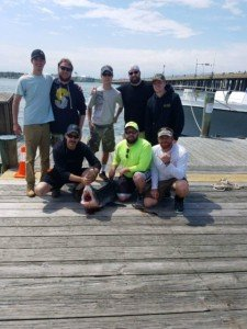 Eight anglers on a dock posing with a large fish