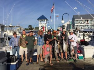 Handful of anglers pose on the dock holding large fish